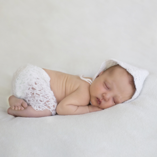 Beautiful baby posed in the Tushie pose using handmade neutral props
