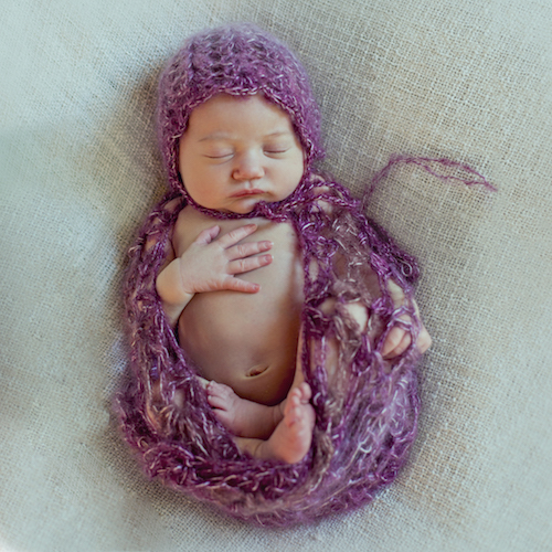 Sleeping newborn all wrapped up in one of a kind handmade prop